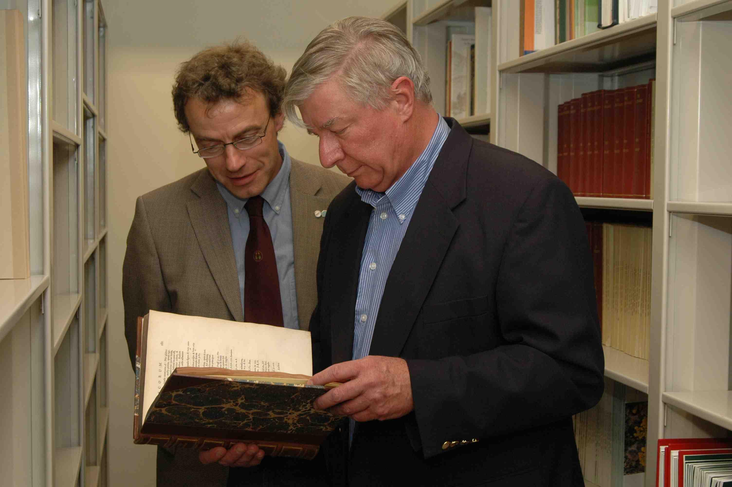 "Storrs L. Olson and B. Goffinet examining Dillenius' 1741 book ""History Muscorum"""